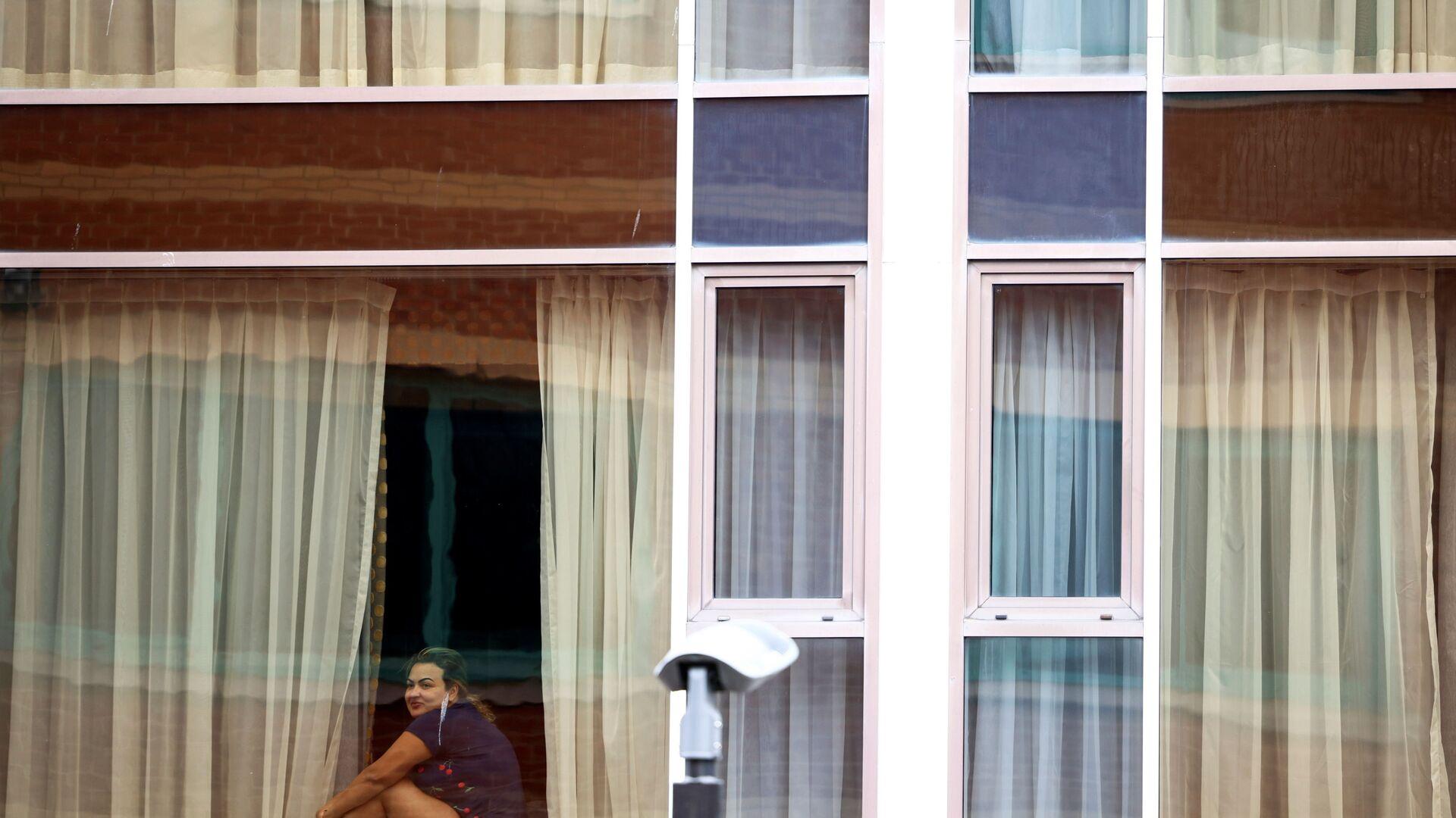 Женщина смотрит из окна отеля Radisson Blu в аэропорту Хитроу, Лондон, Великобритания - Sputnik Латвия, 1920, 01.03.2021