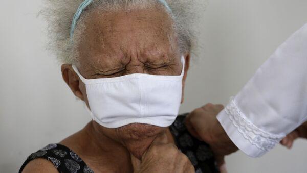 90-летняя Жюстина Батиста во время вакцинации против COVID-19 китайской вакциной Sinovac в Бразилиа, Бразилия - Sputnik Латвия