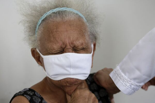 90-летняя Жюстина Батиста во время вакцинации против COVID-19 китайской вакциной Sinovac в Бразилиа, Бразилия - Sputnik Latvija