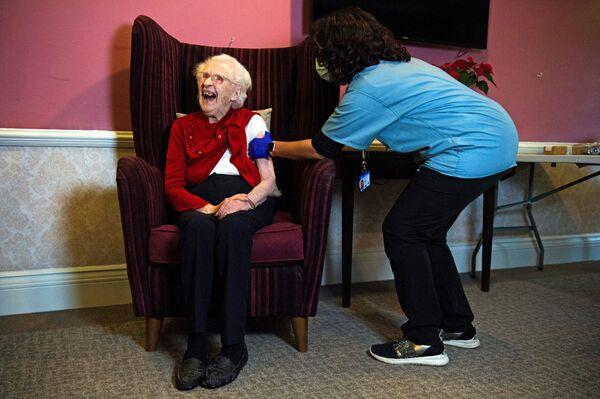 Столетняя жительница дома престарелых в Лондоне во время вакцинации против COVID-19 вакциной Oxford/AstraZeneca - Sputnik Latvija