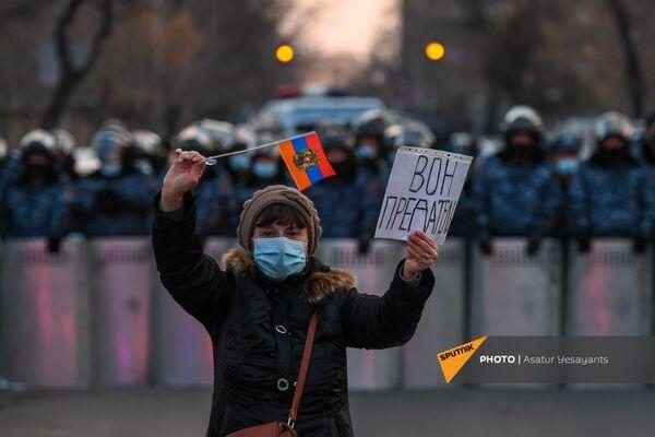 Aktīviste ar plakātu un karogu policijas kordona priekšā opozīcijas mītiņa laikā Bagramjana prospektā pie Armēnijas Nacionālās sapulces ēkas, 3. marts, Erevāna - Sputnik Latvija