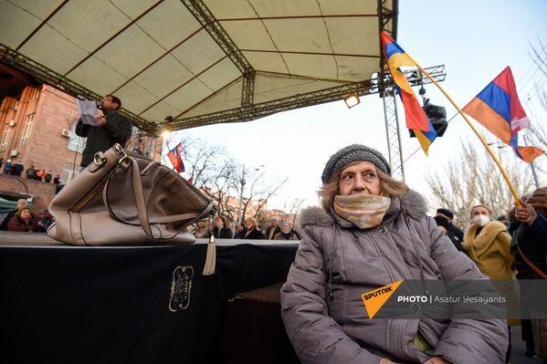 Aktīviste klausās opozīcijas politiķa Gegama Manukjana runu opozīcijas mītiņa laikā Bagramjana prospektā pie Armēnijas Nacionālās sapulces ēkas, 3. marts, Erevāna - Sputnik Latvija