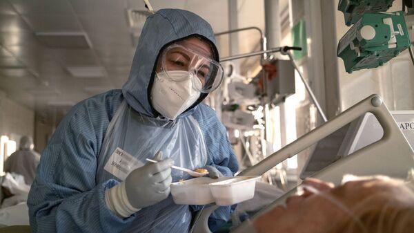 Медсестра кормит пациента в отделении реанимации - Sputnik Латвия