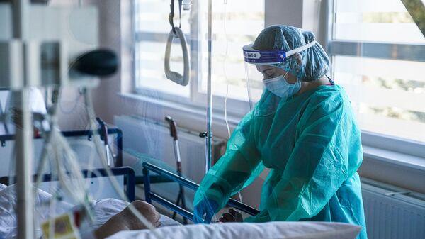 Медсестра оказывает помощь пациенту с COVID-19 в палате интенсивной терапии в коронавирусном отделении Даугавпилсской региональной больницы - Sputnik Латвия