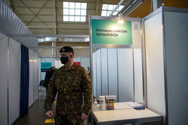 Военный у стойки предвакцинационных консультаций. - Sputnik Латвия