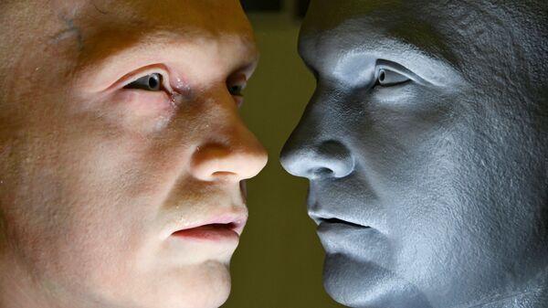 Голова робота-гуманоида (слева), разработанного компанией Promobot, рядом с моделью головы - Sputnik Латвия