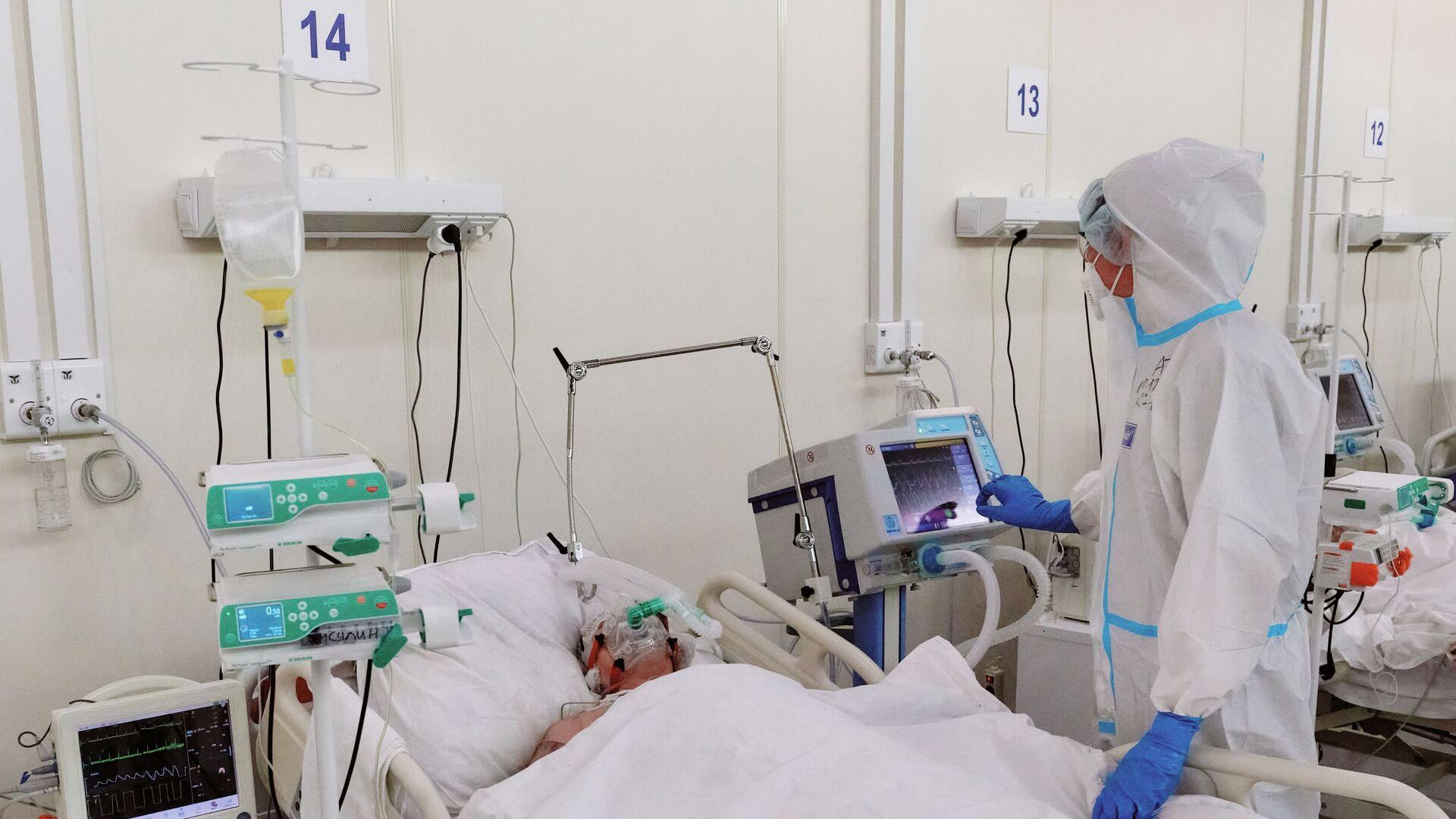 Медсестра у пациента в реанимационном блоке во временном госпитале для больных COVID-19 - Sputnik Латвия, 1920, 22.09.2021