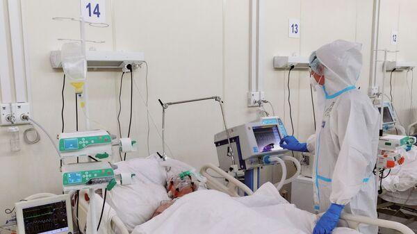 Медсестра у пациента в реанимационном блоке во временном госпитале для больных COVID-19 - Sputnik Латвия