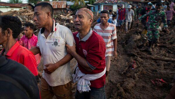Люди оплакивают родственников, погибших в результате стихийного бедствия в индонезийской провинции Восточная Нуса - Тенггара - Sputnik Латвия