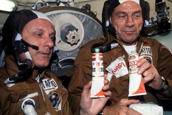 Amerikāņu astronauti Tomass Stafords un Donalds Kents Diks Sleitons ar padomju ēdiena tūbiņām Sojuz orbitālajā modulī. Konteineram ar boršču pielīmēta etiķete degvīns - Sputnik Latvija