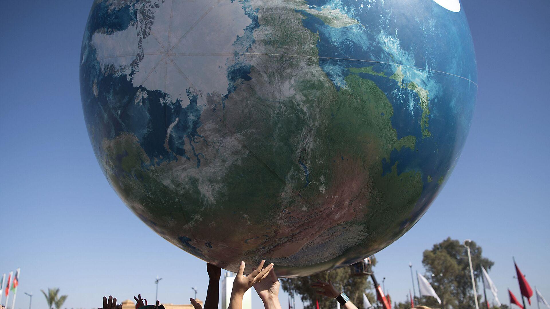 Члены всемирной конференции ООН по вопросам изменения климата с макетом Земли - Sputnik Латвия, 1920, 19.06.2021