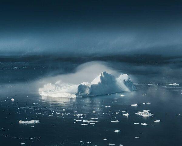 Aisbergi izpeld no miglas kā gigantiskas baltas pilis pie Grenlandes rietumu piekrastes. Laiva kreisajā pusē no ledus kalna dāvā priekšstatu par tā izmēriem - Sputnik Latvija
