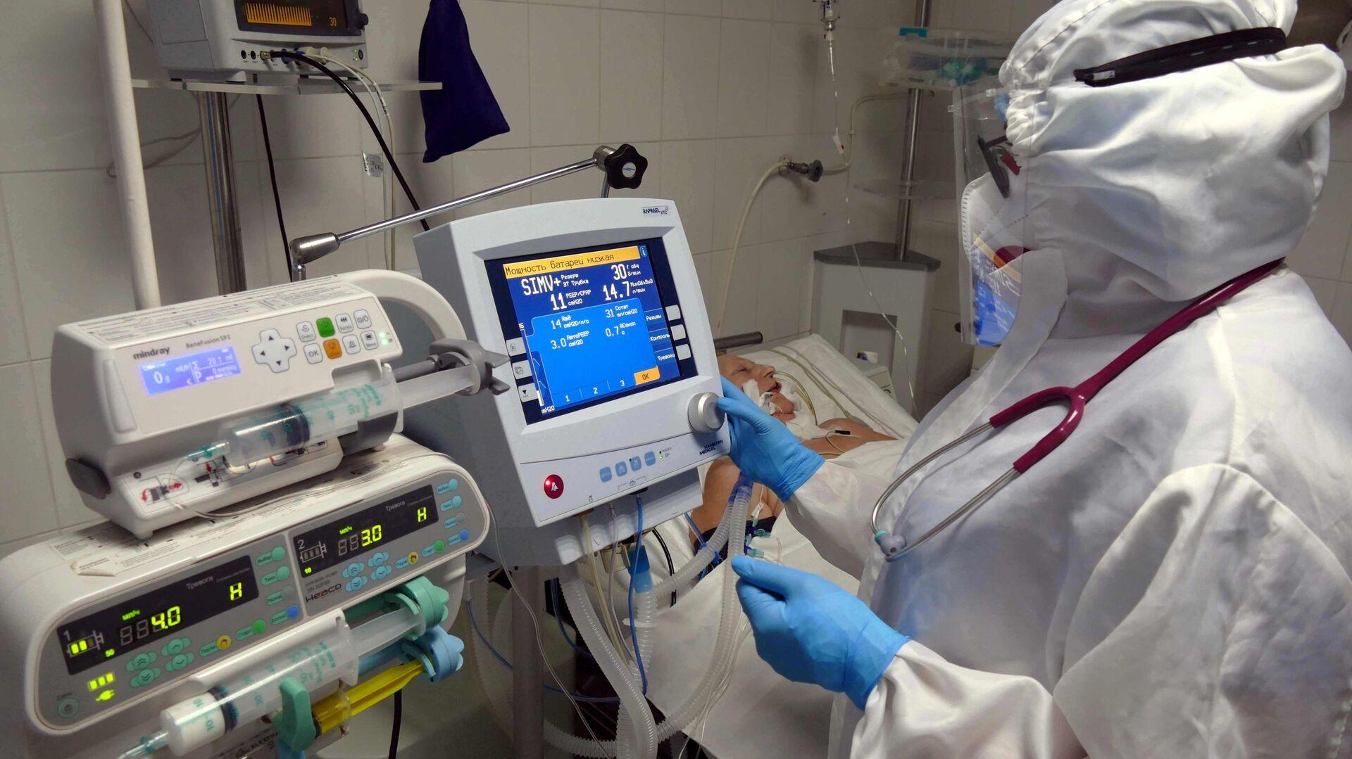 Медицинский работник и пациент в отделении анестезиологии и интенсивной терапии в клинической больнице, где оказывают медицинскую помощь больным с COVID-19. - Sputnik Латвия, 1920, 08.09.2021