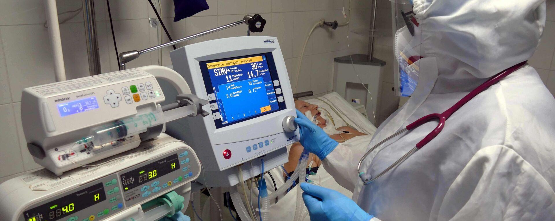 Медицинский работник и пациент в отделении анестезиологии и интенсивной терапии в клинической больнице, где оказывают медицинскую помощь больным с COVID-19. - Sputnik Latvija, 1920, 02.05.2021
