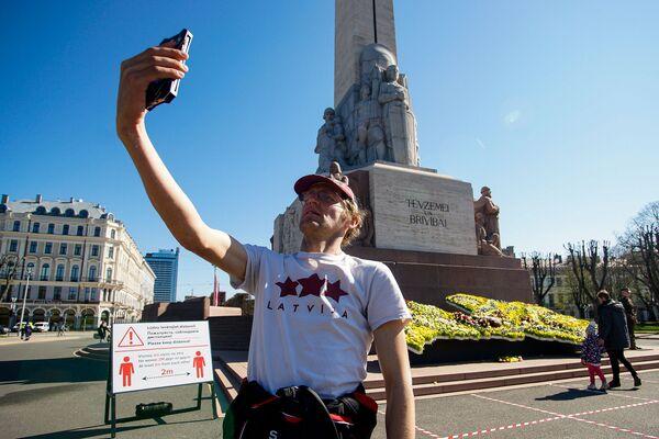 Vīrietis fotografējas pie Brīvības pieminekļa Latvijas neatkarības atjaunošanas dienā - Sputnik Latvija