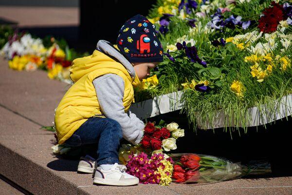 Bērns ar rozēm Latvijas karoga krāsās pie Brīvības pieminekļa Latvijas neatkarības atjaunošanas dienā - Sputnik Latvija