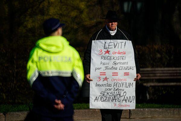 Latvijas antiglobālists Sigurds Graudiņš ar plakātu Latvijas neatkarības atjaunošanas dienā - Sputnik Latvija