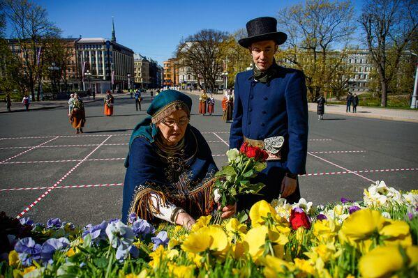 Sieviete un vīrietis tautastērpos noliek ziedus pie Brīvības pieminekļa Latvijas neatkarības atjaunošanas dienā - Sputnik Latvija