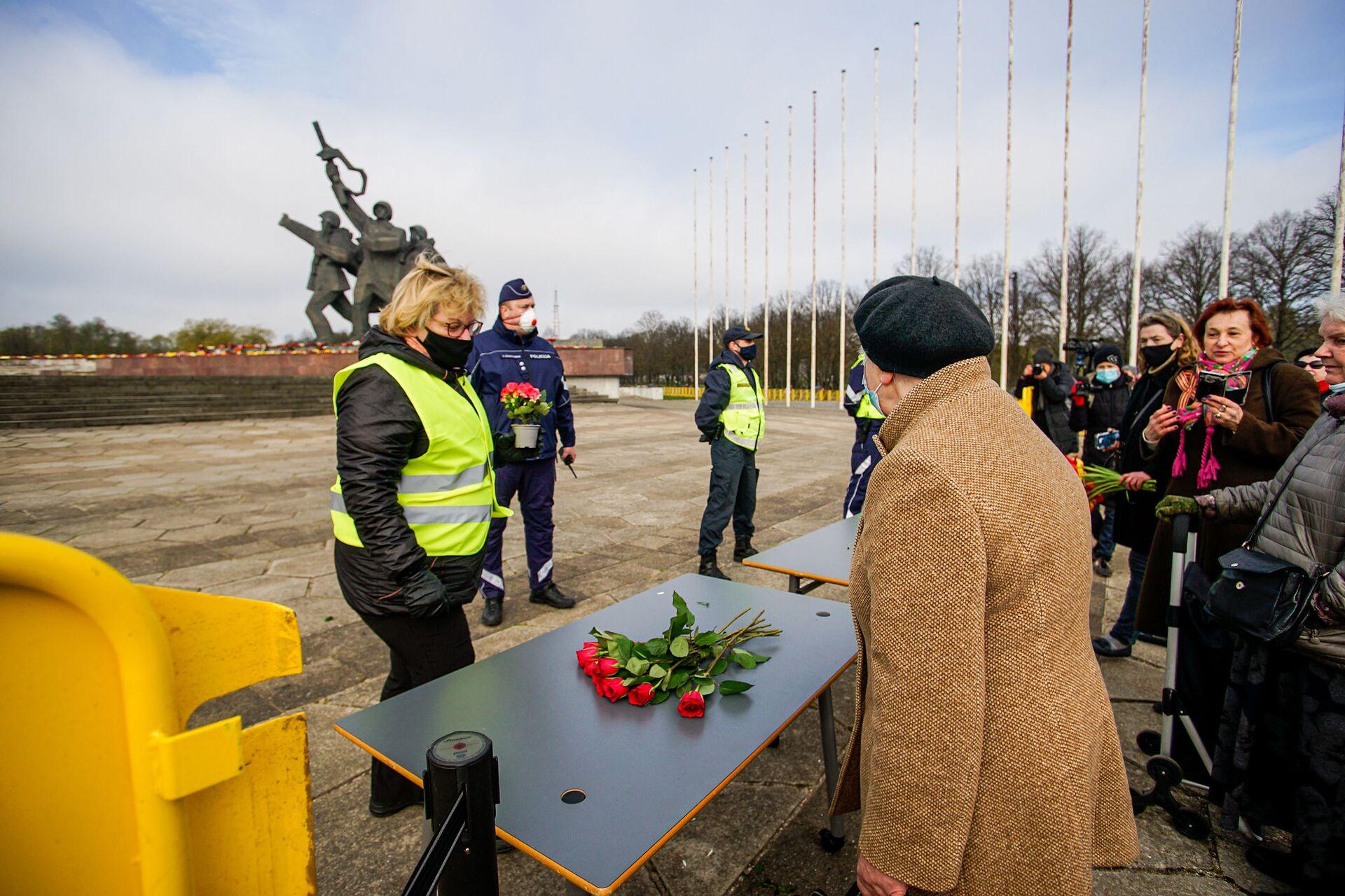 Цветы предлагают оставлять на столах, установленных возле памятника - Sputnik Latvija, 1920, 01.06.2021