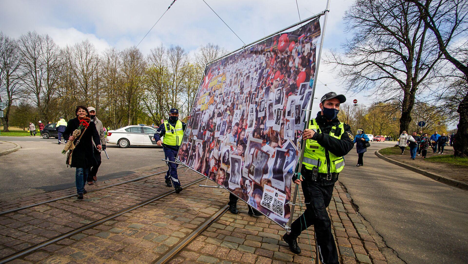 Полицейские помогают нести плакат, посвященный Бессмертному полку - Sputnik Latvija, 1920, 09.05.2021