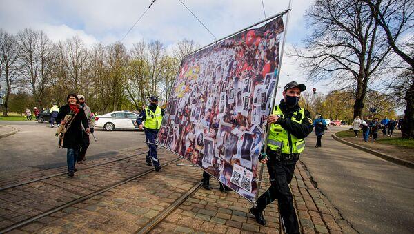 Полицейские помогают нести плакат, посвященный Бессмертному полку - Sputnik Latvija