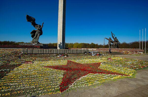 Sarkanā zvaigzne no ziediem pie Uzvaras pieminekļa, ko izkārtojuši brīvprātīgie - Sputnik Latvija