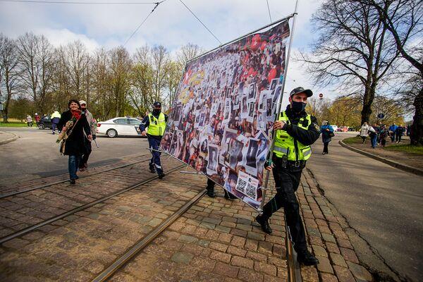 Policisti palīdz nest Nemirstīgajam pulkam veltīto plakātu - Sputnik Latvija