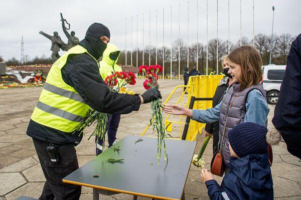 Cilvēki atstāj ziedus uz galdiem netālu no pieminekļa, pēc tam ziedus nes uz monumentu - Sputnik Latvija