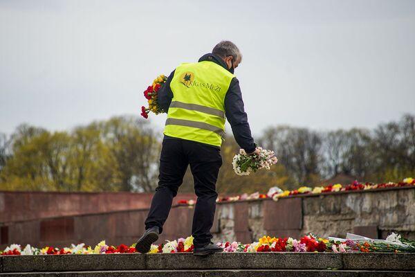 Rīgas meži darbinieks novieto ziedus pie Uzvaras pieminekļa - Sputnik Latvija