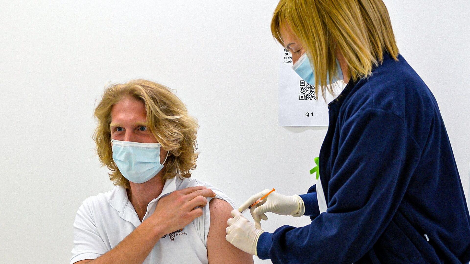 Мужчина во время вакцинации от COVID-19 российским препаратом Sputnik V (Гам-КОВИД-Вак) в Сан-Марино - Sputnik Латвия, 1920, 17.06.2021