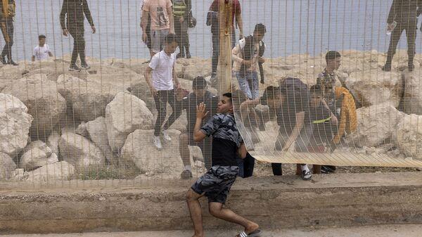 Марокканские мигранты после попытки пересечь границу между Марокко и испанским анклавом Сеута - Sputnik Латвия