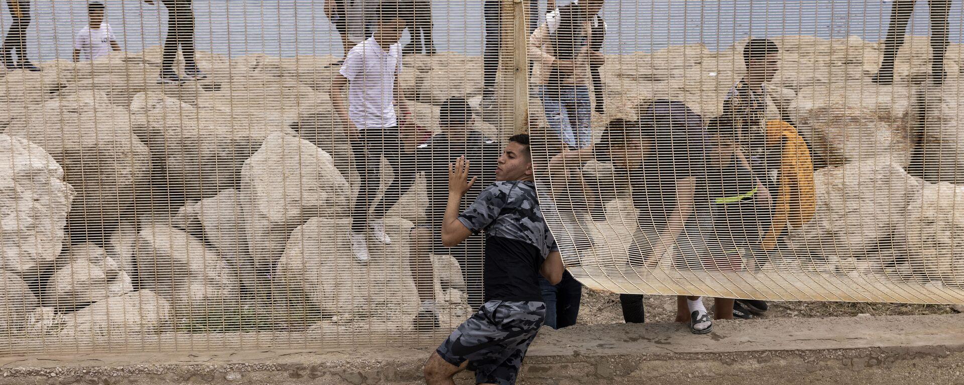 Марокканские мигранты после попытки пересечь границу между Марокко и испанским анклавом Сеута - Sputnik Латвия, 1920, 14.07.2021