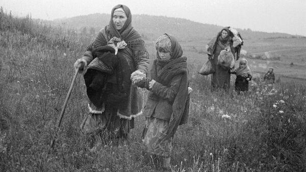 Женщины и дети идут через поле в освобожденные Красной Армией деревни. Прибалтийский фронт. - Sputnik Latvija