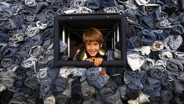 Zēns pabāzis galvu no vitrīnas ar 33 088 pāriem džinsu, ko savāca žurnāls National Geographic Kids pārstrādei par siltumizolācijas materiālu mājokļiem Vašingtonā, 2009. gads. Šis zēns savāca 1684 pārus - Sputnik Latvija