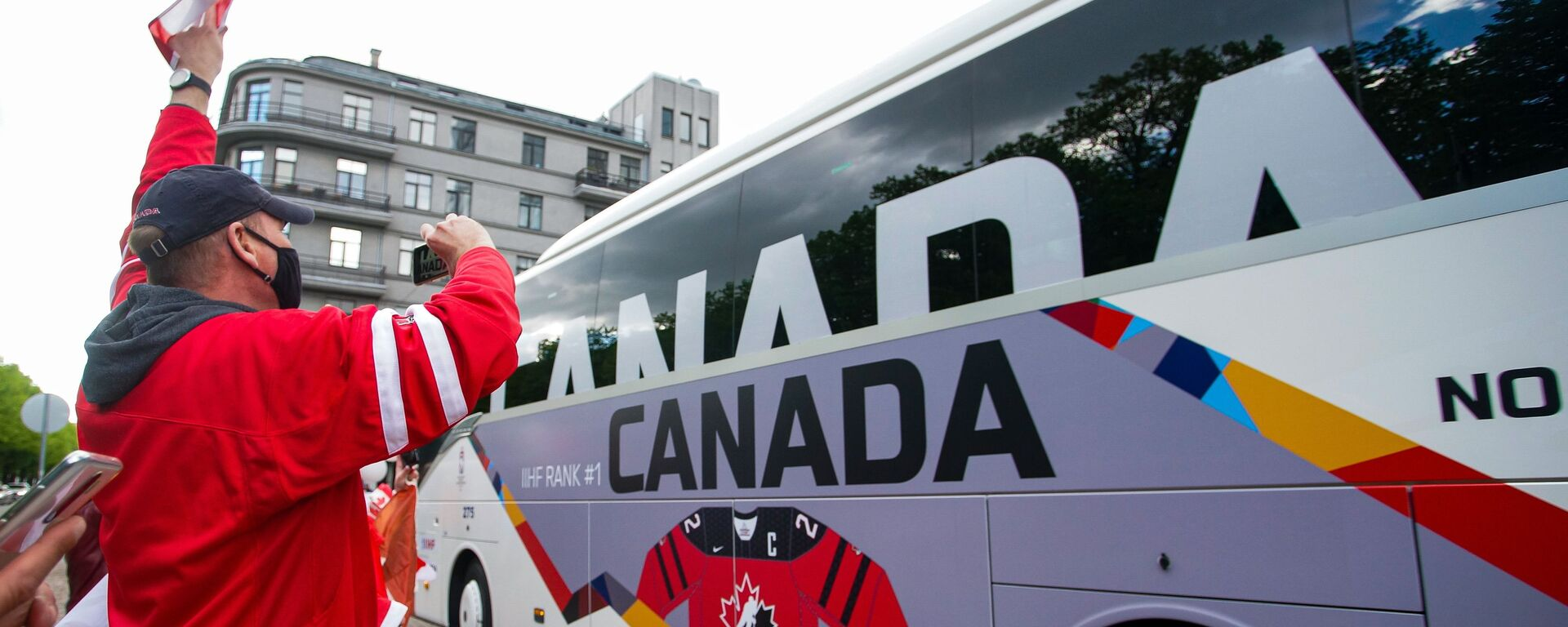 Болельщики сборной Канады приветствуют автобус с игроками команды перед матчем чемпионата мира по хоккею 2021 против сборной Латвии. - Sputnik Латвия, 1920, 26.05.2021
