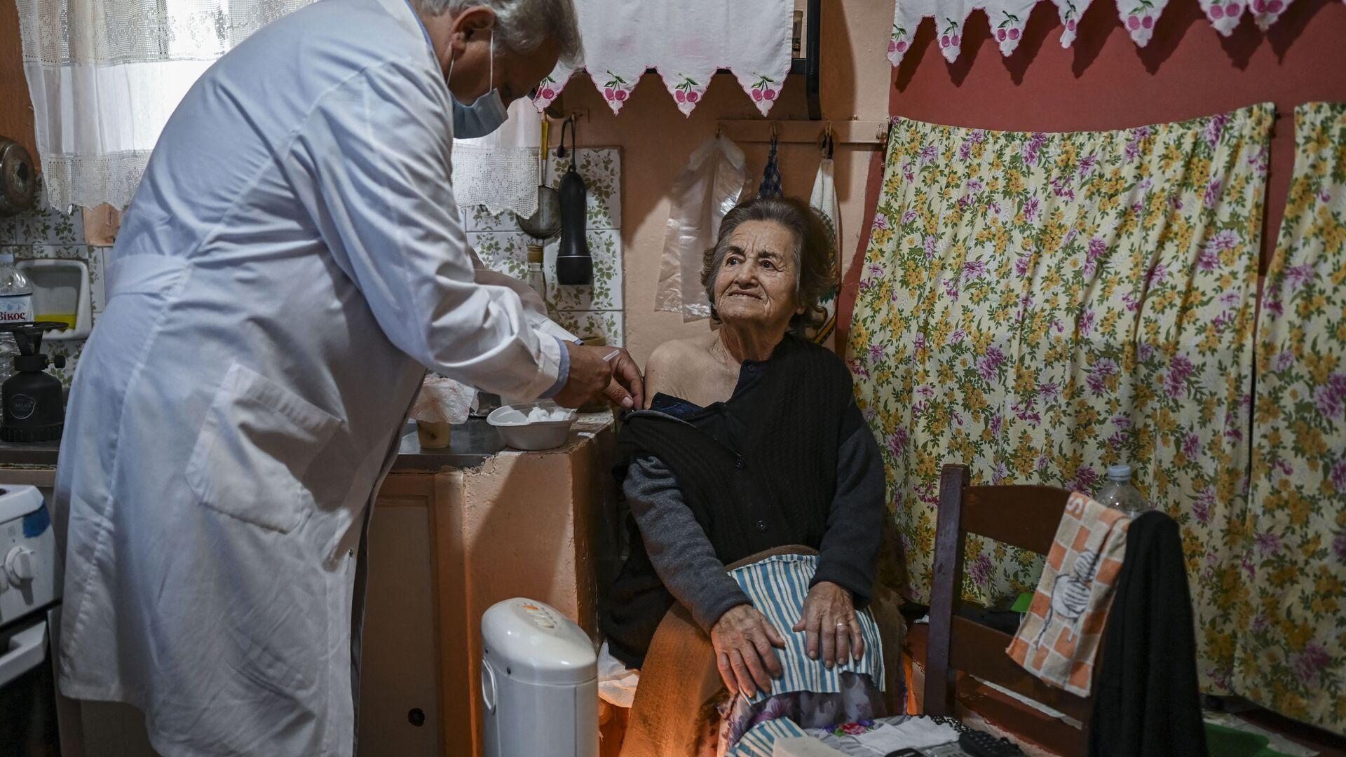 Доктор Анаргирос Мариолис вакцинирует пожилую женщину от Covid-19 на острове Элафониссос - Sputnik Латвия, 1920, 17.06.2021