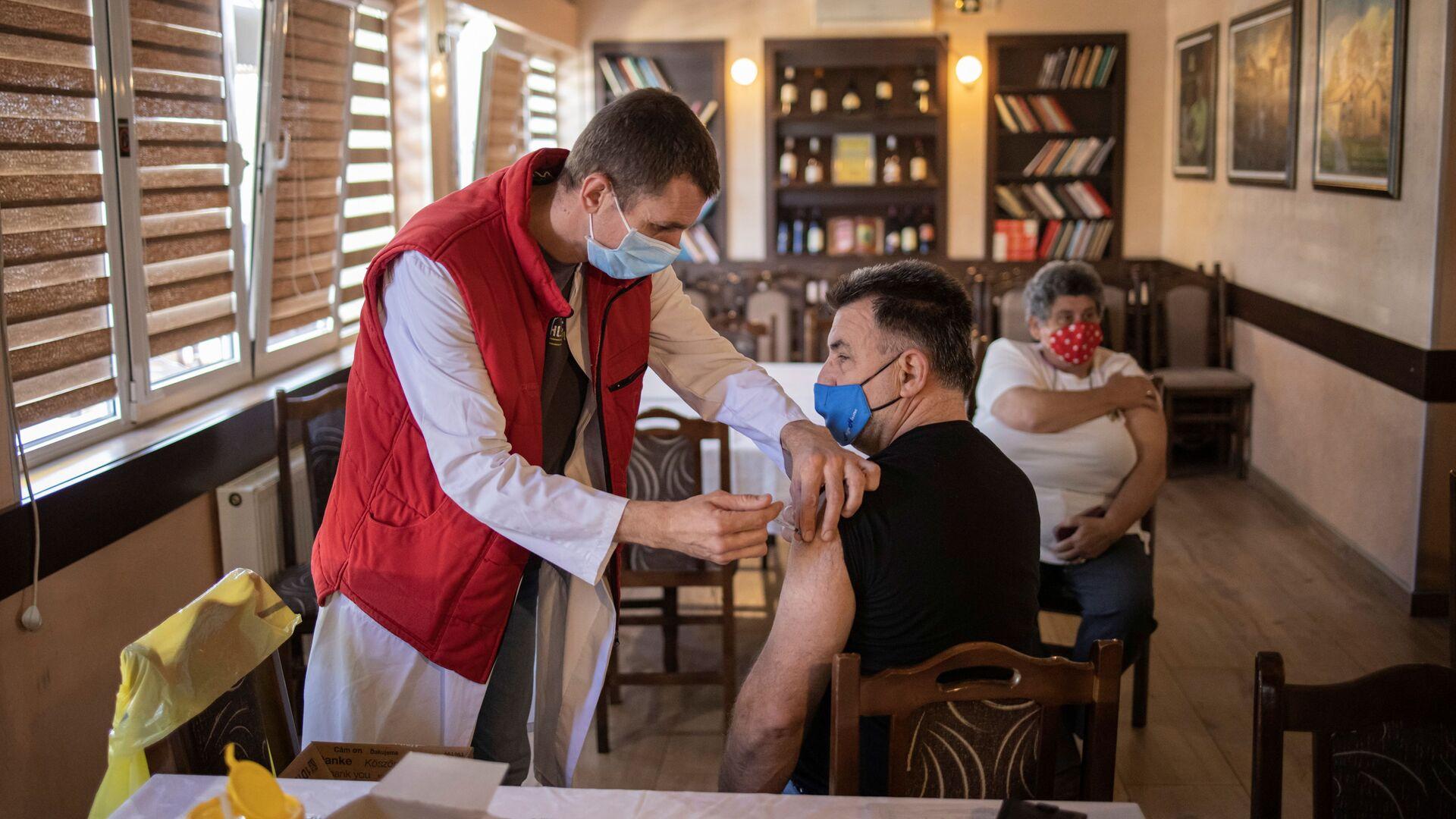 Мужчина получает дозу китайской вакцины Sinopharm против коронавирусной болезни (COVID-19) в ресторане в Крагуеваце, Сербия - Sputnik Латвия, 1920, 14.06.2021
