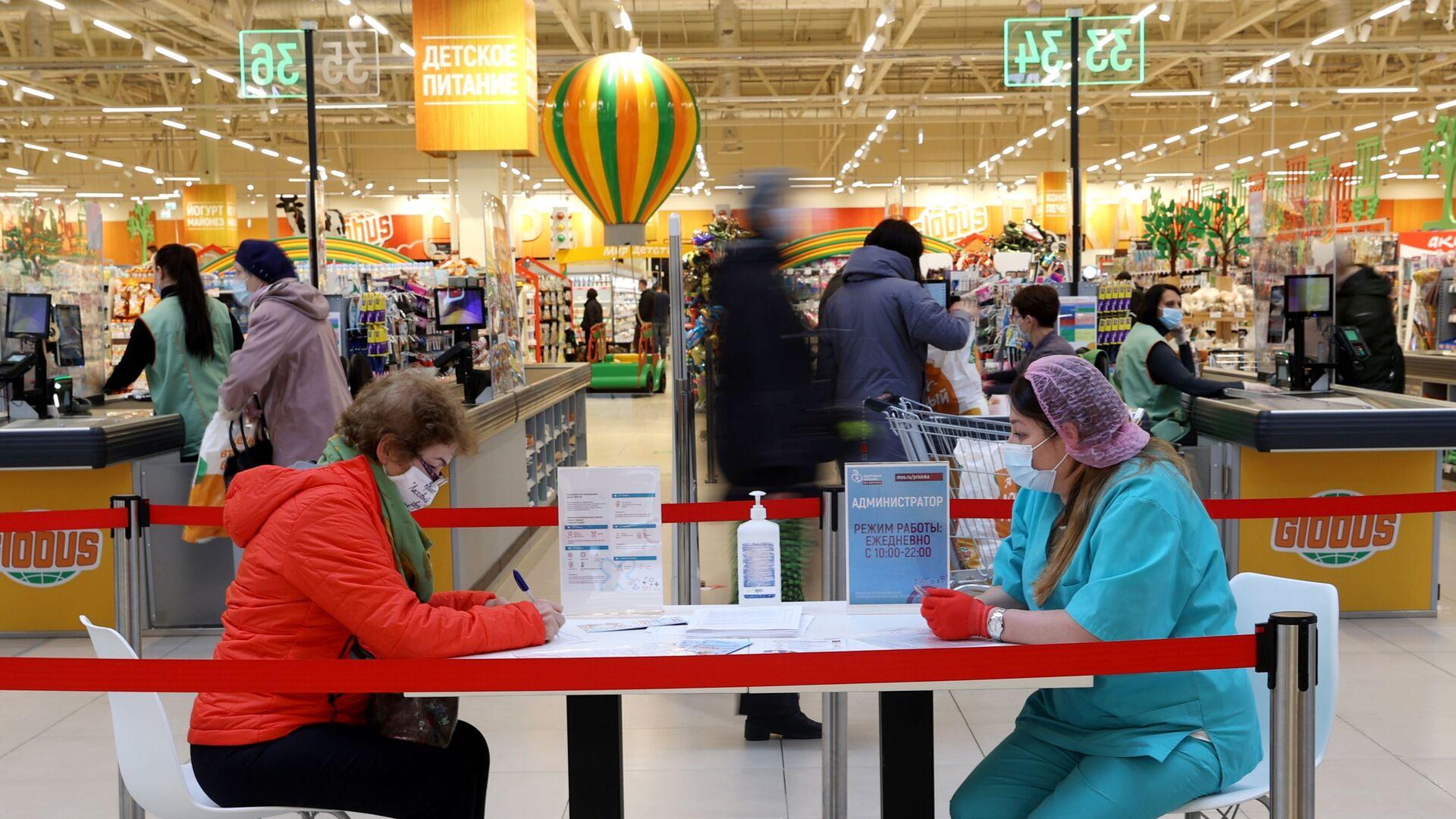Женщина заполняет документы перед вакцинацией от COVID-19 российской вакциной Спутник V (Гам-КОВИД-Вак) в гипермаркете Глобус в Москве - Sputnik Латвия, 1920, 31.05.2021