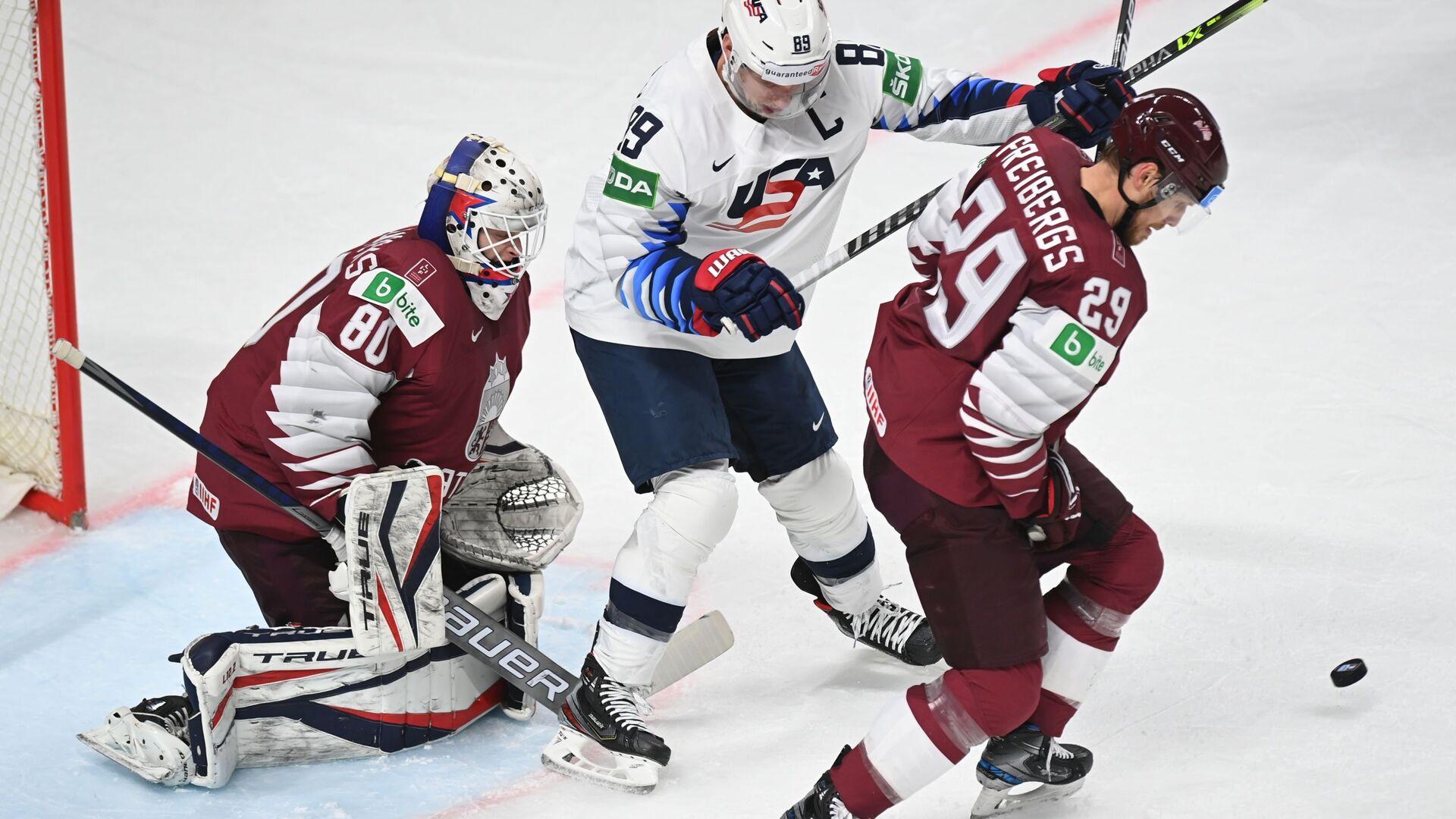 Слева направо: вратарь Матис Кивлениекс (Латвия), Джастин Абделкейдер (США) и Ральф Фрейбергс (Латвия) в матче группового этапа ЧМ по хоккею 2021 - Sputnik Латвия, 1920, 05.07.2021