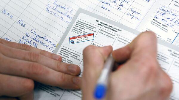 Ветеринарный врач делает отметку в паспорте животного после вакцинации от COVID-19 в ветеринарной клинике в Москве - Sputnik Латвия