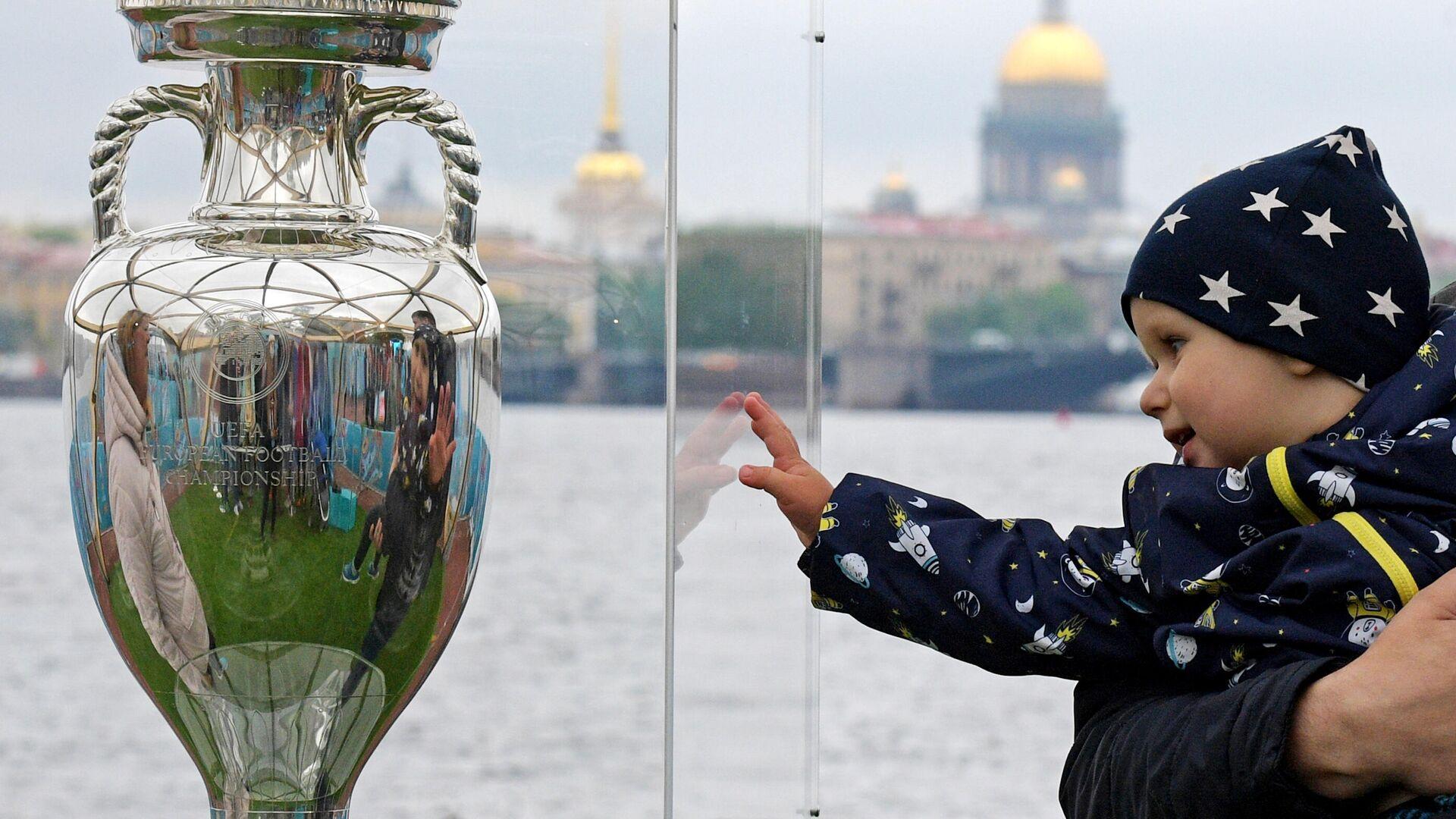 Ребенок рядом с кубком Европы по футболу, представленным в Санкт-Петербурге - Sputnik Латвия, 1920, 02.06.2021