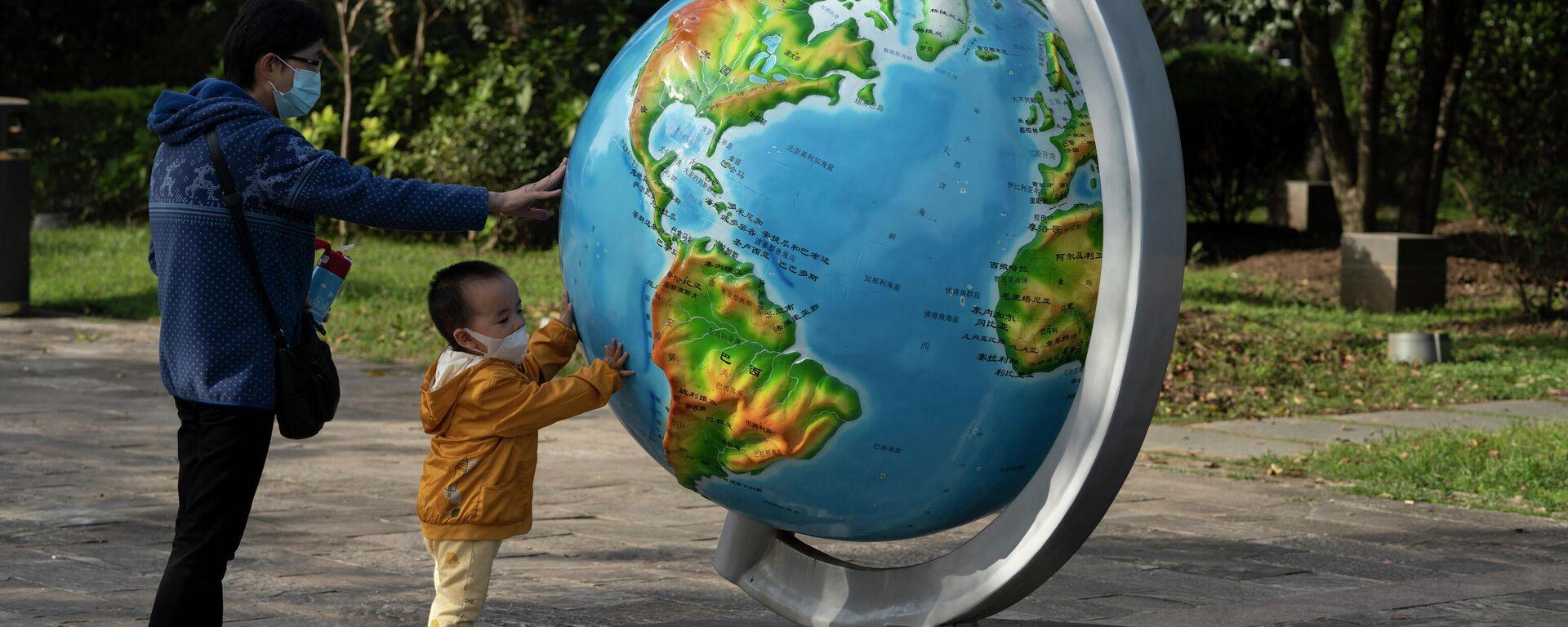 Женщина с ребенком у глобуса в парке в Ухани, Китай - Sputnik Латвия, 1920, 31.08.2021
