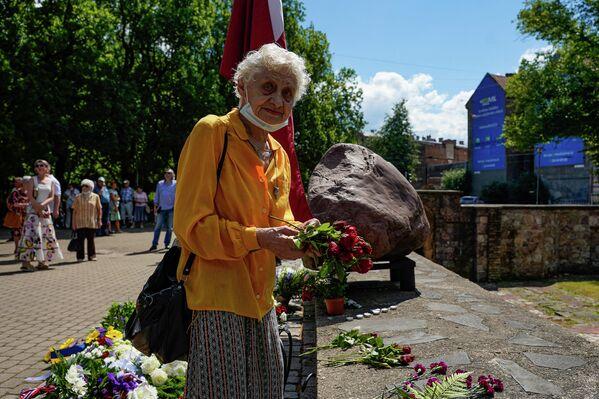 Женщина возлагает цветы к мемориалу Большой хоральной синагоги в День памяти геноцида еврейского народа в Латвии. - Sputnik Латвия