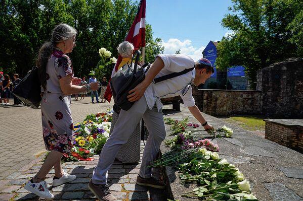 Люди возлагают цветы к мемориалу Большой хоральной синагоги в День памяти жертв геноцида еврейского народа в Латвии. - Sputnik Латвия