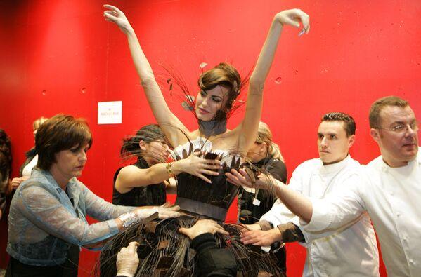 Шеф-кондитеры и стилисты завершают шоколадное платье испанской модели, телеведущей и певицы Ирен Сальвадор перед показом модных шоколадных платьев в рамках 12-й Всемирной выставки шоколада в Париже, 27 октября 2006 года. - Sputnik Латвия