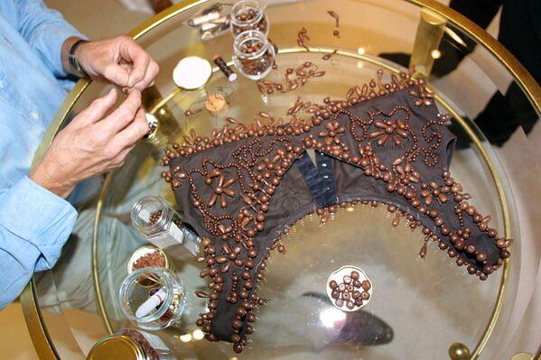 Шоколатье Анри Леру пришивает шоколадные жемчужины на бюстье, предназначенное для ношения поверх платья, во время примерки с актрисой Габриель Лазюр в Париже, 31 октября 2001 года. - Sputnik Латвия