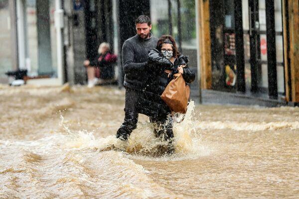 Мужчина помогает женщине пробираться по затопленной улице в бельгийском городе Спа. 14 июля 2021 года. - Sputnik Латвия