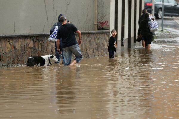 Люди пытаются пройти по затопленной улице немецкого города Хаген. 14 июля 2021 года. - Sputnik Латвия