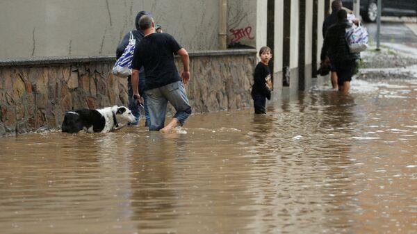 Люди идут по затопленной улице после проливных дождей в Хагене, Германия - Sputnik Латвия