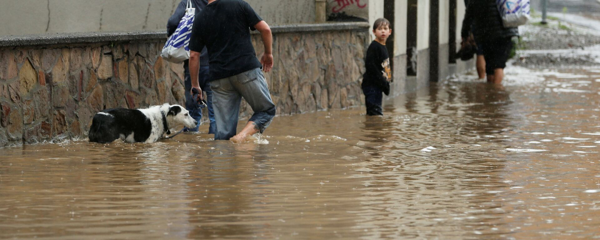 Люди идут по затопленной улице после проливных дождей в Хагене, Германия - Sputnik Латвия, 1920, 26.07.2021